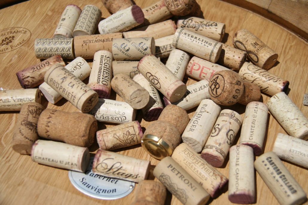 Photo of various used wine corks on wine barrel top by Phil Bourke