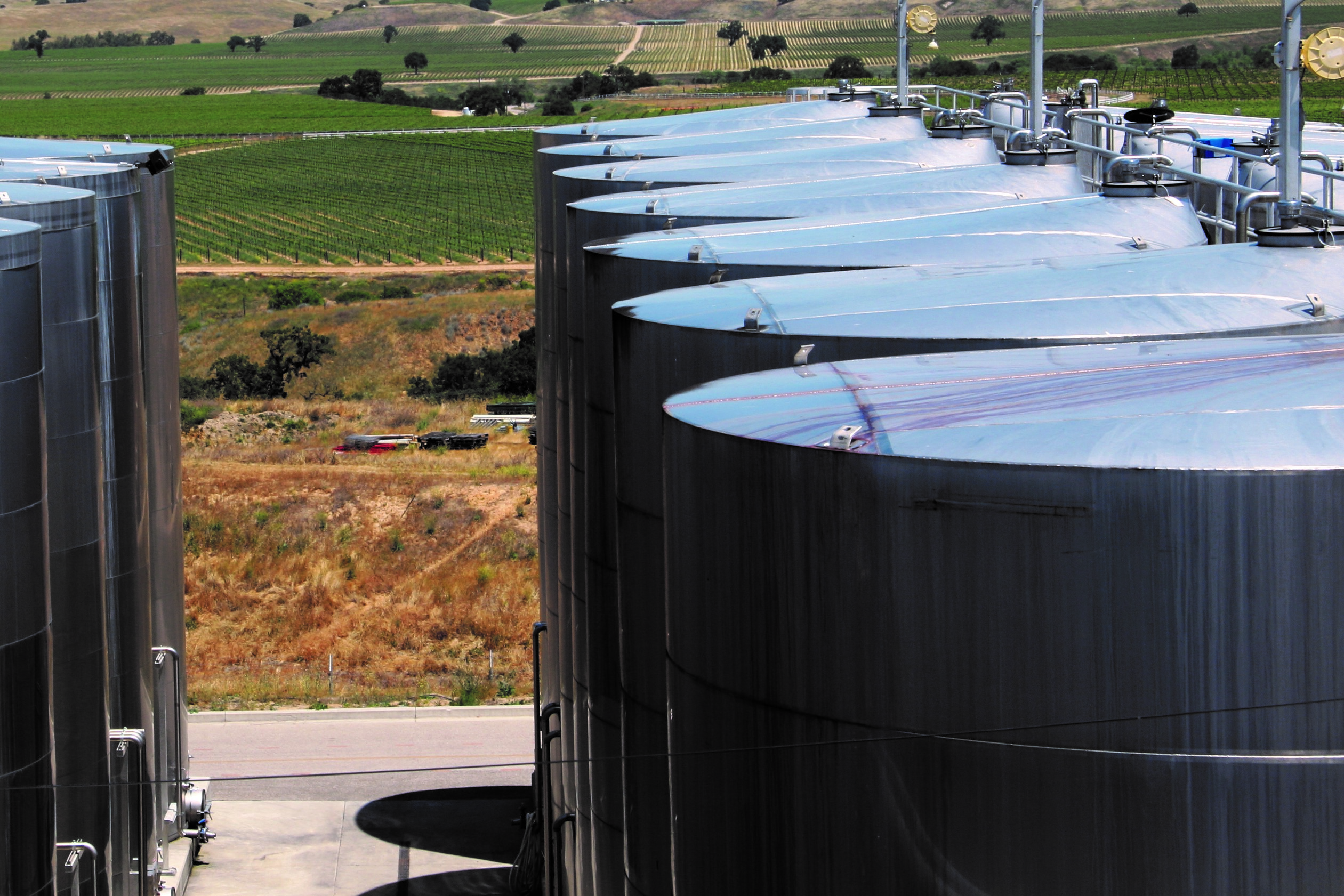 Photo of wine tanks with vineyards in background by Phil Bourke